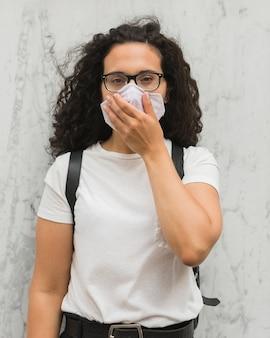 Mulher cobrindo a boca enquanto usava máscara médica