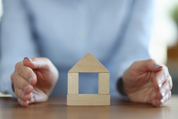 Mulher cobrindo a casa de madeira com a mão fechada