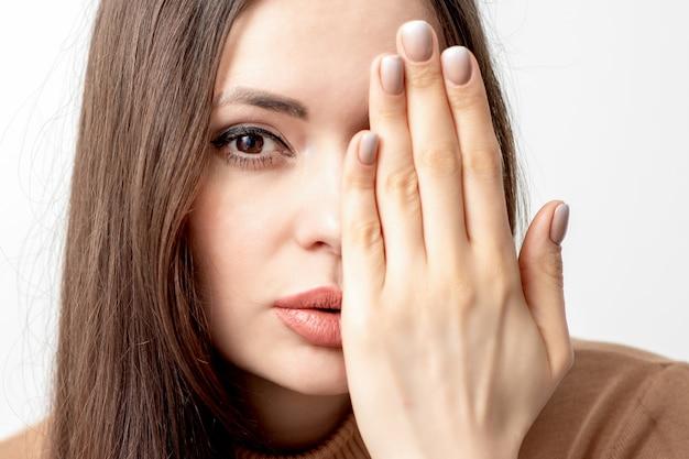 Mulher cobrindo metade do rosto com a mão