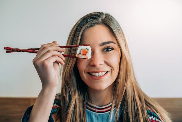 Mulher cobrindo o olho com um pedaço de sushi