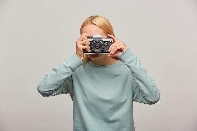 Mulher cobrindo o rosto com a câmera fazendo uma sessão de fotos