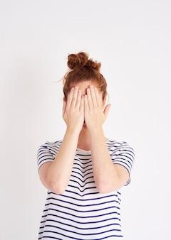 Mulher cobrindo o rosto com as mãos atiradas