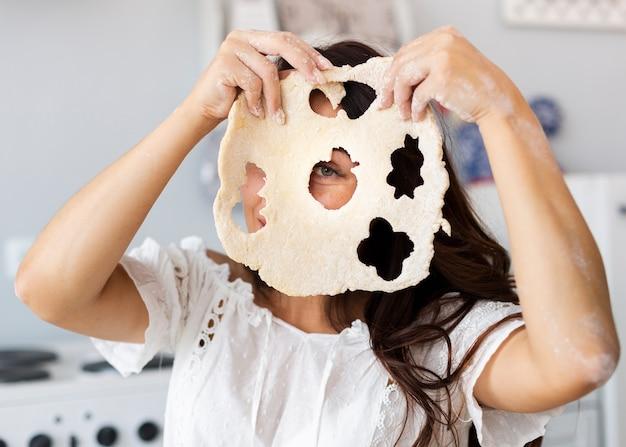 Mulher cobrindo o rosto com massa de biscoitos