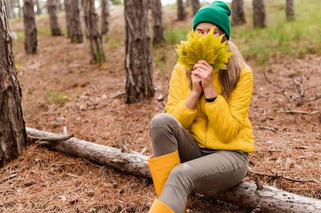 Mulher cobrindo o rosto com um monte de folhas de outono