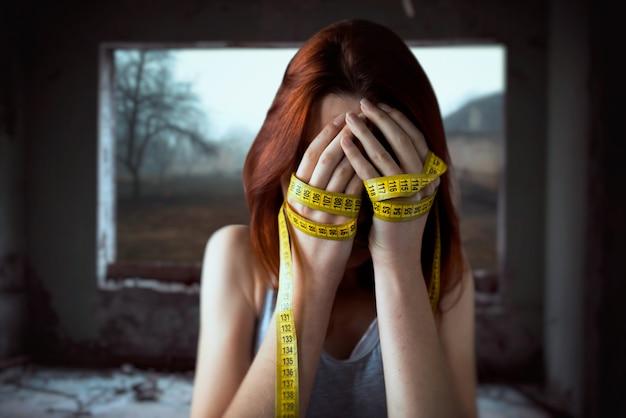 Mulher cobrindo o rosto, mãos amarradas com fita métrica