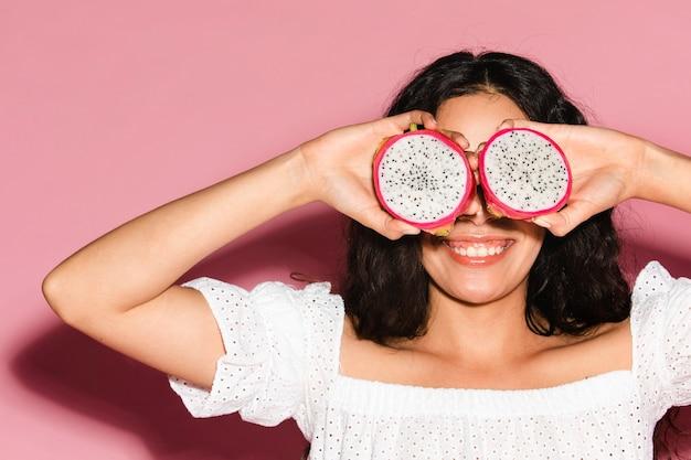Mulher cobrindo os olhos com frutas fatiadas de dragão