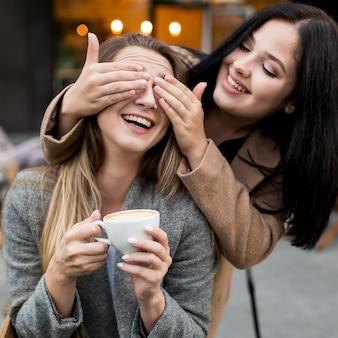 Mulher cobrindo os olhos da amiga