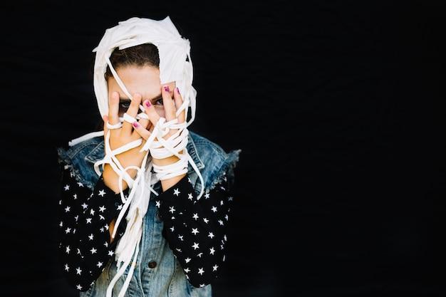 Mulher cobrindo rosto com ligaduras