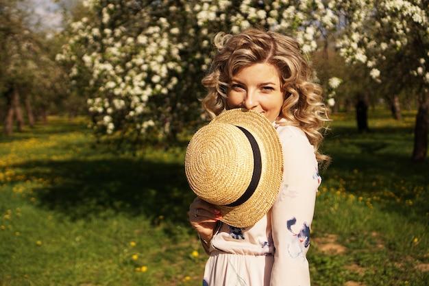 Mulher cobriu metade do rosto com um chapéu de palha - momentos felizes no jardim verde - primavera e verão