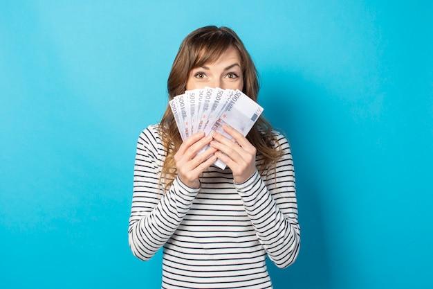 Mulher cobriu o rosto com um fã de dinheiro