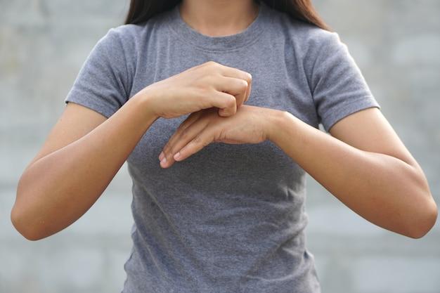 Mulher coçando o braço de coceira em fundo cinza claro. causa da coceira na pele inclui picadas de inseto