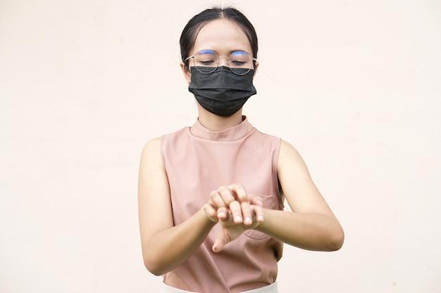 Mulher coçando o braço de coceira em fundo cinza claro