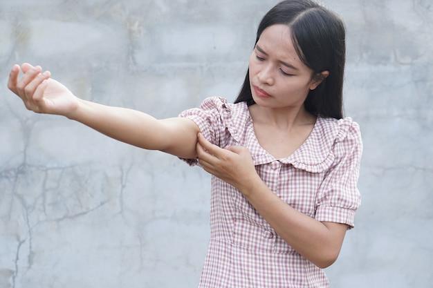Mulher coçando o braço de coceira em fundo cinza