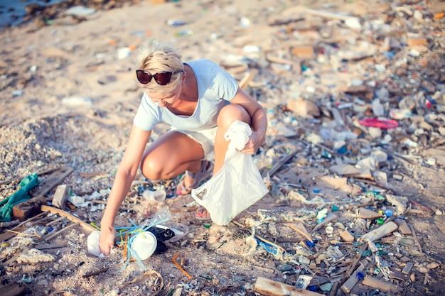 Mulher coleta lixo na praia. conceito de proteção ambiental