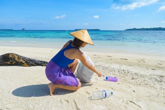 Mulher coletando garrafas de plástico na bela praia tropical, conceito de reciclagem