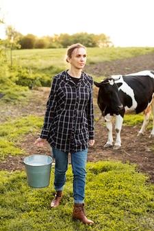 Mulher coletando leite de vaca