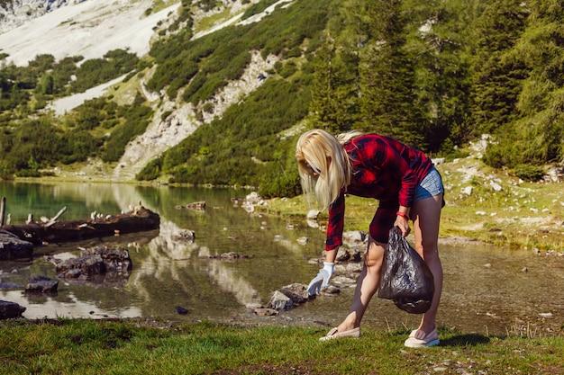 Mulher coletando lixo da grama na montanha