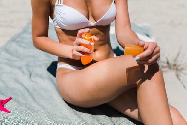Mulher colheita, aplicando lotion suntan, ligado, perna