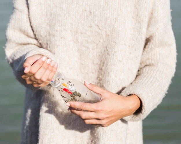 Mulher colhendo plástico da beira-mar