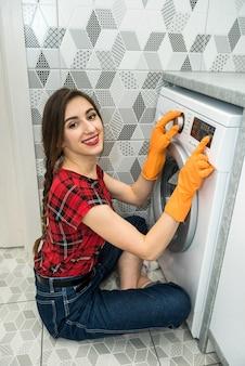 Mulher coloca a roupa na máquina de lavar.