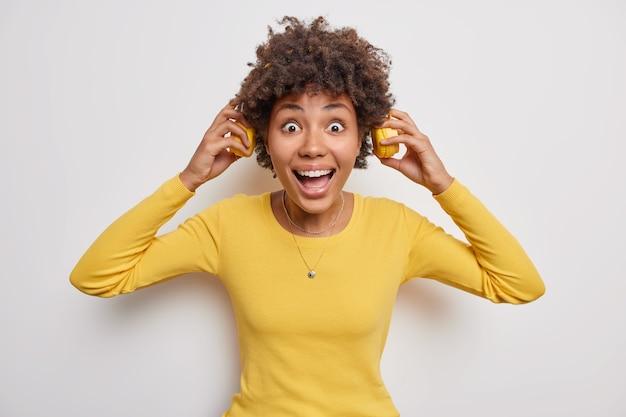 Mulher coloca fones de ouvido com olhar louco ouve música em fones de ouvido estéreo usa suéter amarelo sobre branco