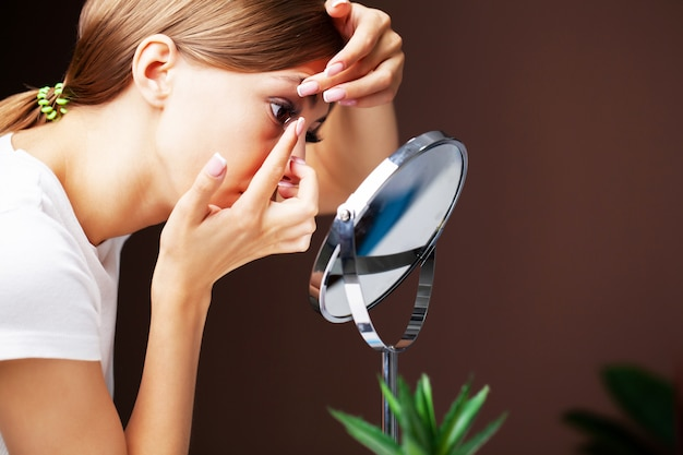 Mulher coloca lentes de contato para visão em casa na frente de um espelho