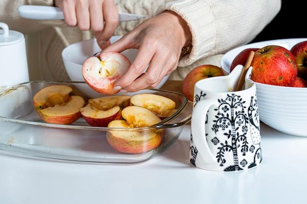 Mulher coloca maçãs cortadas à mão em uma tigela de vidro e as prepara para assar, conceito de cozimento caseiro para o feriado
