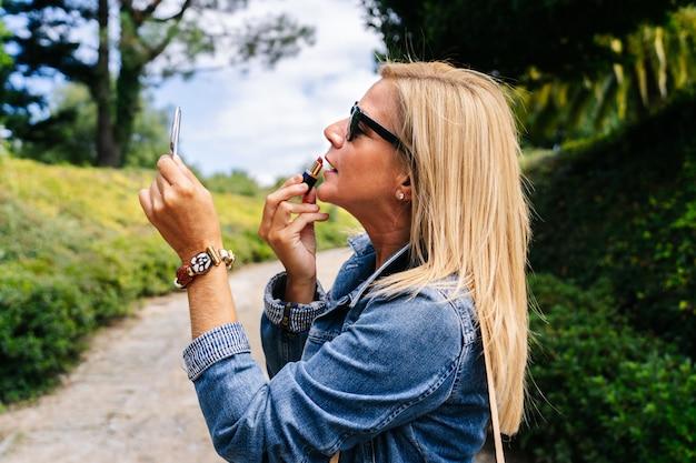 Mulher coloca maquiagem no parque