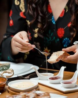 Mulher coloca mel no pão na instalação de pequeno-almoço tradicional