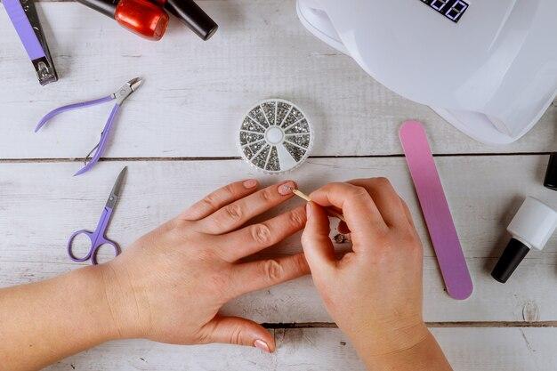 Mulher coloca strass na unha fazendo gel manicure.