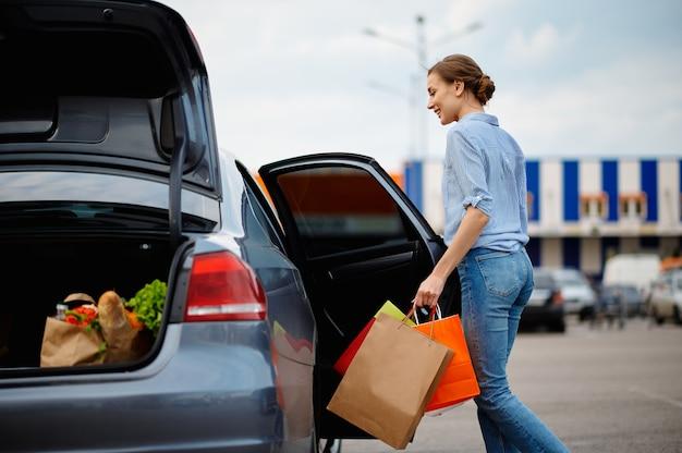 Mulher coloca suas compras no carro, no estacionamento do mercado. cliente feliz carregando compras do shopping center, veículos