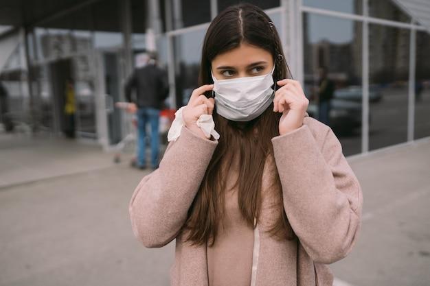 Mulher coloca uma máscara protetora médica.