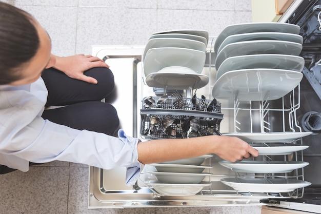 Mulher colocando a louça na máquina de lavar louça na cozinha do apartamento dela