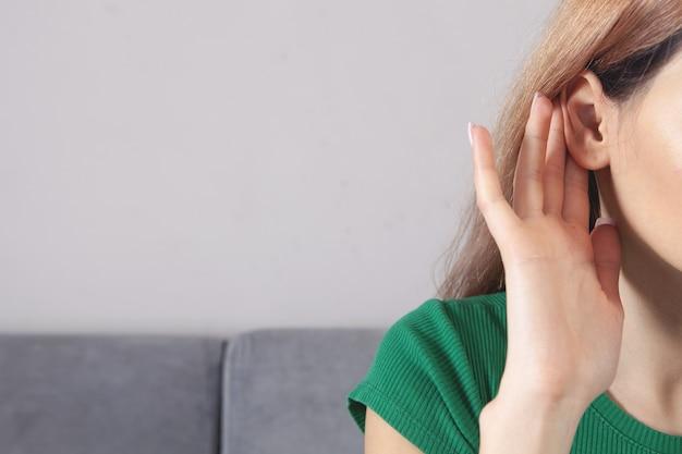 Mulher colocando a mão perto da orelha e ouvindo