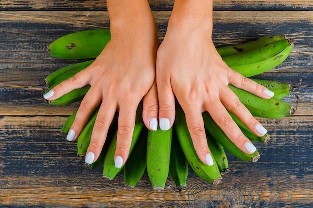 Mulher colocando as mãos em bananas verdes