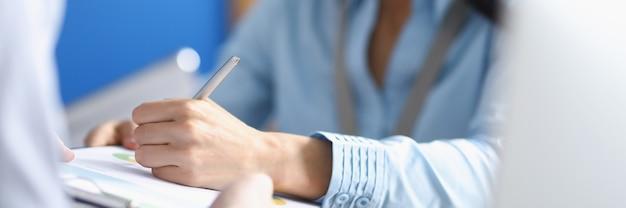 Mulher colocando assinatura com caneta esferográfica em documento, na área de transferência, close-up