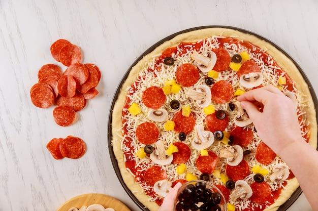 Mulher colocando azeitonas na pizza crua crua.