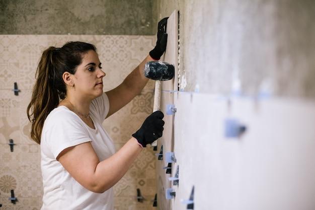 Mulher colocando azulejos em um banheiro novo