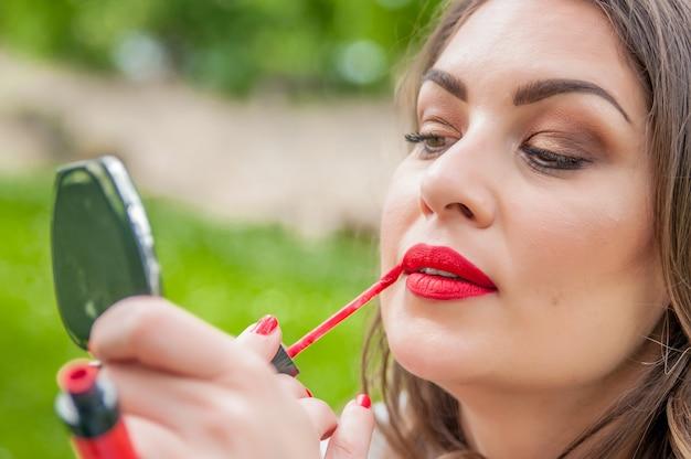 Mulher colocando, corrigindo o brilho labial do batom vermelho. cafeteria, restaurante, urbano, ao ar livre, fundo. modelo de raça mista