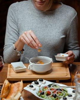 Mulher colocando cubos de recheio de pão em sua sopa de cogumelos, servida com salada grega