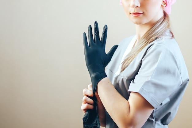 Mulher colocando em luvas de borracha preta, ela em traje cinza corpo e cuidados de saúde