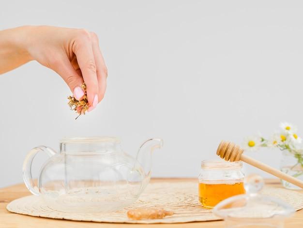 Mulher colocando ervas secas no bule de chá