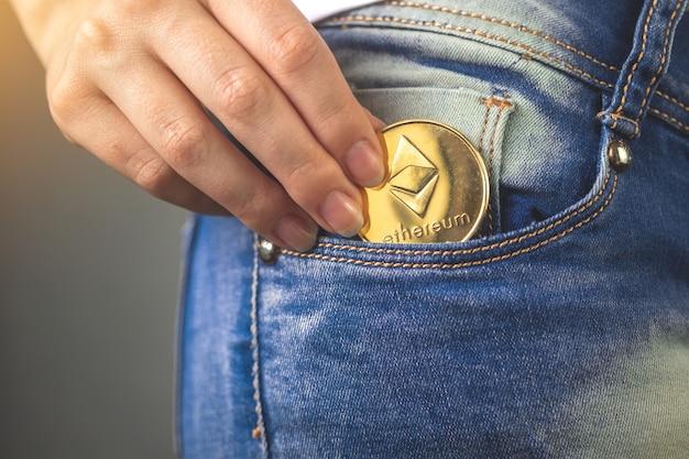 Mulher colocando ethereum eth no bolso da calça jeans, moeda dourada da criptomoeda na foto do fundo do bolso