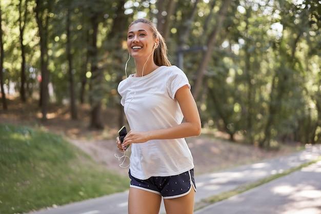 Mulher colocando fones de ouvido para ouvir música antes de correr no parque de verão