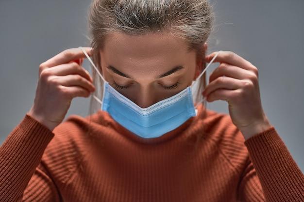 Mulher colocando máscara protetora médica para proteção da saúde e prevenção de vírus da gripe, epidemias e doenças infecciosas.