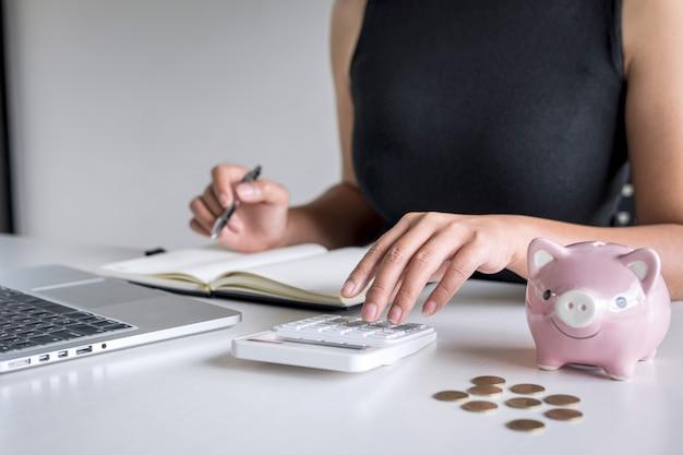 Mulher colocando moedas de ouro no cofrinho rosa para intensificar o crescimento dos negócios para lucrar e economizar com o cofrinho, economizando dinheiro para o plano futuro e o conceito de fundo de aposentadoria