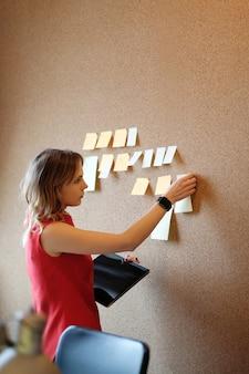 Mulher colocando notas auto-adesivas na parede