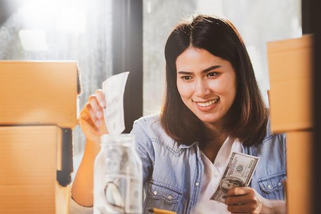 Mulher colocando notas de dinheiro para a garrafa de vidro para poupar dinheiro.