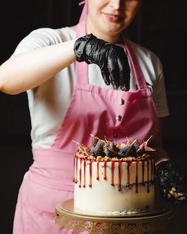 Mulher colocando nozes em cima do bolo clássico decorado com figos e calda