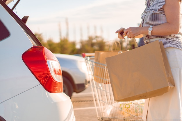 Mulher colocando sacos de papel com comida no porta-malas do carro